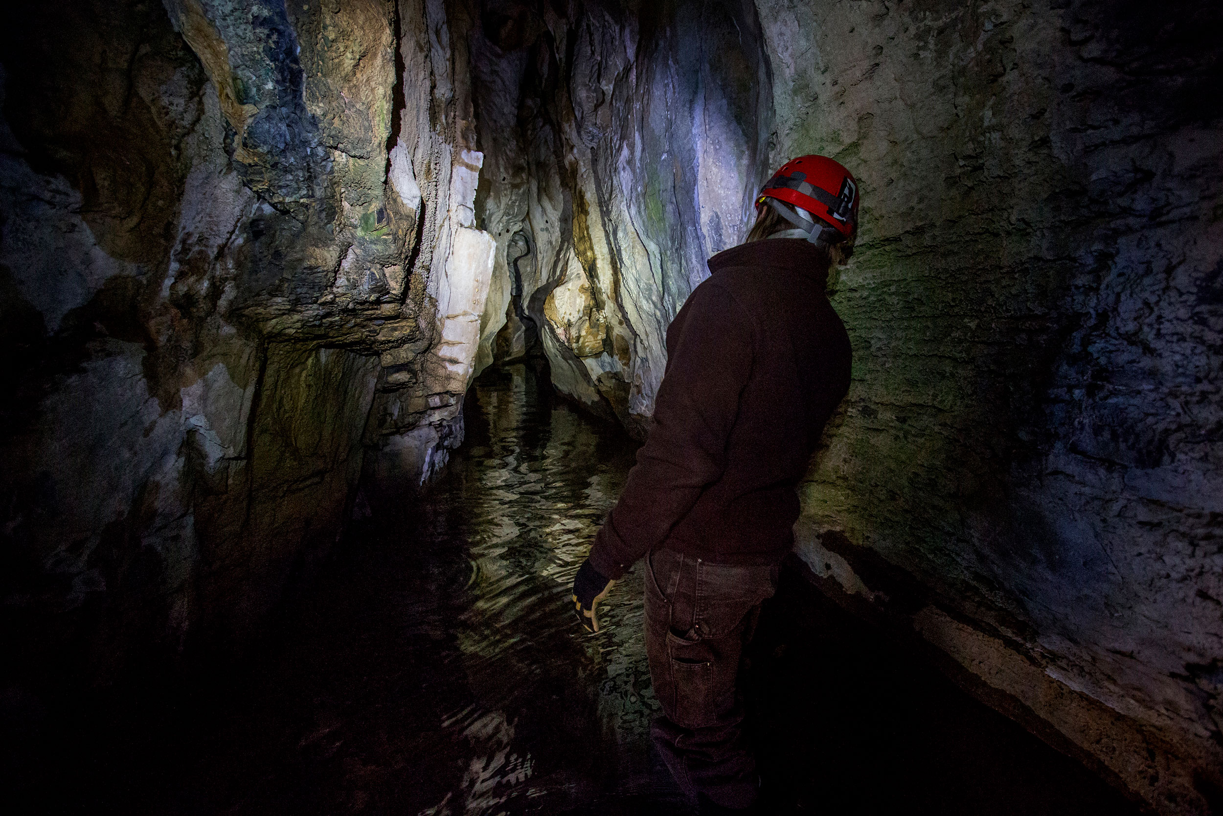 Wildlife biologist Adam Brewerton checks the water level in Logan Cave on Wednesday, Feb. 15. The mile-long cave was dry at the start of February, but by the middle of the month, a heavy stream of water was pouring out of the cave due to warm weather and melting snow.