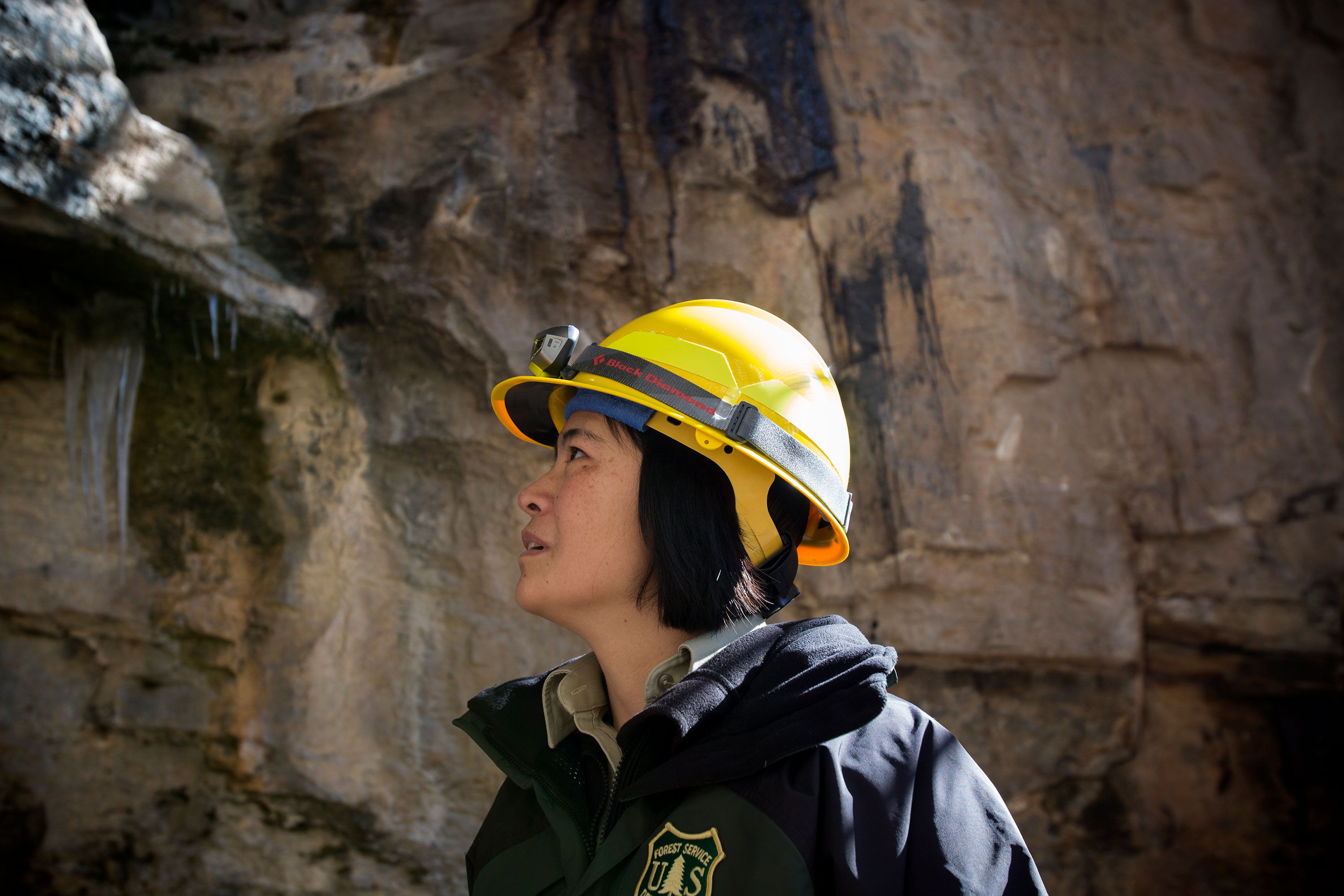 Wildlife biologist Masako Wright examines the entrance of Logan Cave on Wednesday, Feb. 15. Forest Service staff are looking for ways to limit access to the cave and protect bats after people began breaking through the current gate.