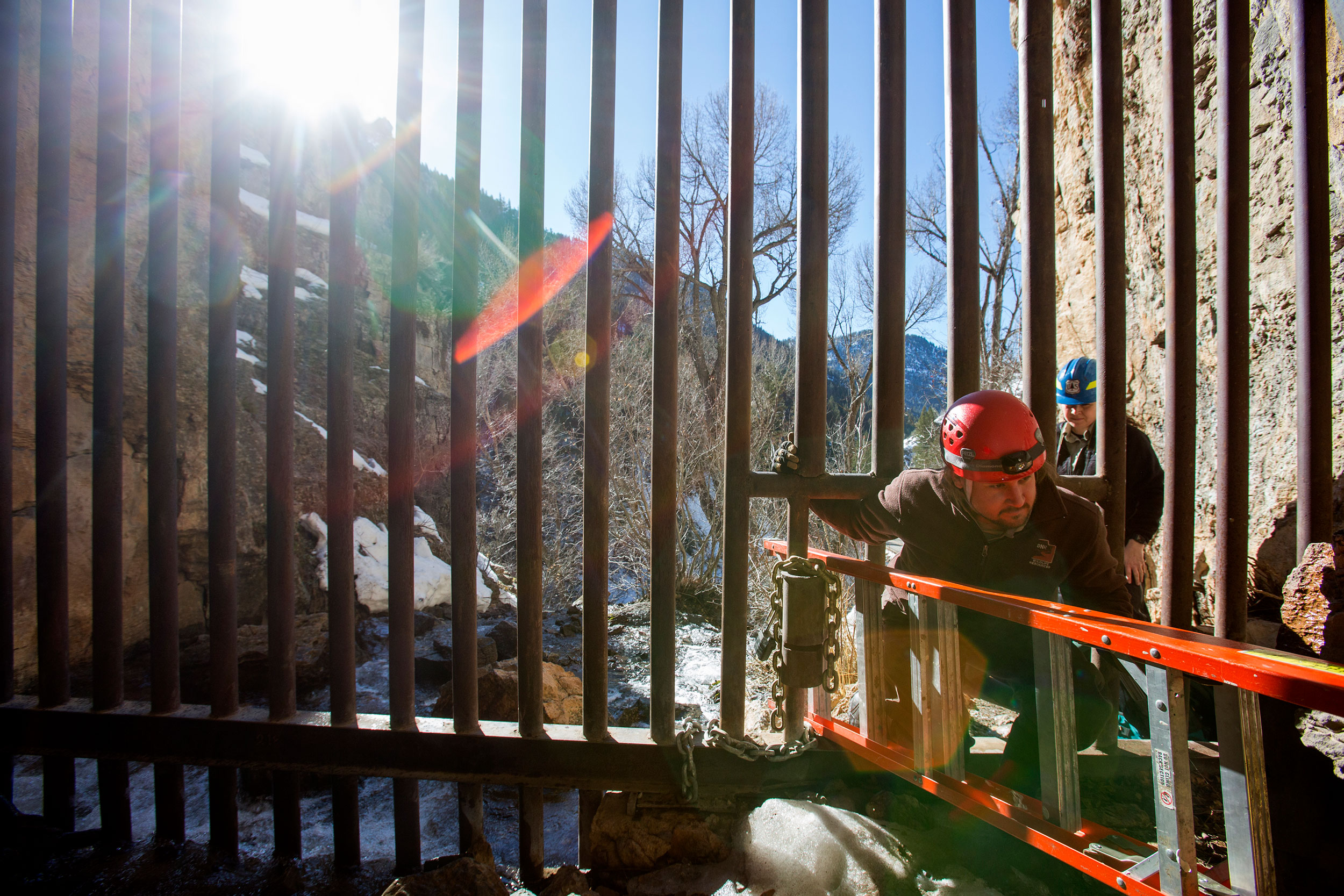 Wildlife biologist Adam Brewerton squeezes into Logan Cave along with a ladder on Wednesday, Feb. 15. Brewerton was examining the cave entrance as part of plans to add a second, more-secure gate.